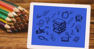 High angle view of various icons in digital tablet by color pencils at table Royalty Free Stock Photo