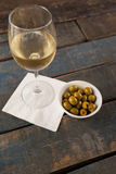 High angle view of  white wine by green olives served in container. High angle view of white wine by green olives served in container on wooden table against Stock Images