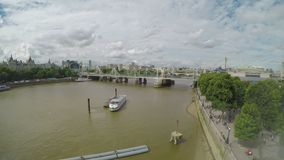 High angle view from window of Thames river and footbridge with cloudy sky and buildings in London - stock video