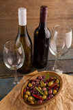 High angle view of wine bottles by olives served in container Stock Image