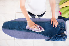 High Angle View Of Woman Ironing Jeans Stock Photography