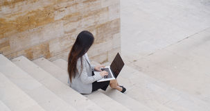 High angle view of woman on laptop on stairs Royalty Free Stock Photo