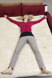 High angle view of woman lying on mattress in furniture store Royalty Free Stock Image