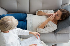 High angle view of woman relaxing on sofa by therapist Stock Image