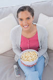 High angle view of woman sitting on sofa holding popcorn Stock Photos