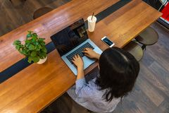High angle view of woman typing laptop on wooden table royalty free stock photography