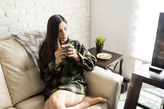 Young Woman In Shirt Sipping Coffee. High angle view of woman wearing checked shirt and drinking coffee on cozy sofa stock photography