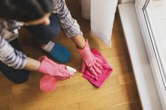 Woman wiping the floor. High angle view of woman wearing protective gloves and cleaning floor with floor disinfectatnt cleaner. Focus on the mop and the fingers stock photo