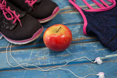 High angle view of womenswear with apple and headphones. On wooden table Stock Photos