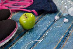 High angle view of womenswear with Granny Smith apple and headphones. On wooden table Stock Photos