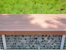 High Angle View of Wooden Plank Bench with Rocks Underneath. High Angle View of Wooden Plank Bench with Rocks and Wire Mesh Underneath stock images