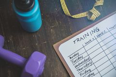 High Angle View Of A Workout Plan In Notebook At Wooden Desk royalty free stock images
