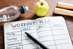 Workout Plan In Notebook. High Angle View Of A Workout Plan In Notebook At Wooden Desk Royalty Free Stock Images
