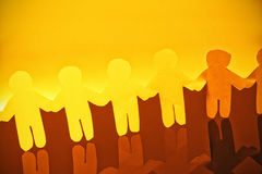 Yellow paper cut out figures making chain on glass table Stock Photos
