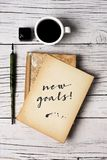 Text new goals in a yellowish note. High angle view of a yellowish notepad with the text new goal written in it, a nib pen, a bottle of writing ink and a cup of Stock Image