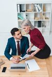 high angle view of young business colleagues flirting while working together royalty free stock images