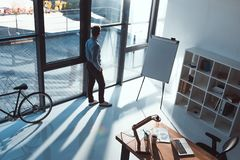 High angle view of young businessman. Looking at window in office royalty free stock images