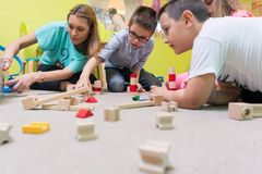Female educator teaching children to build a train circuit. High-angle view of a young female educator teaching children to build with patience a wooden train Royalty Free Stock Photo