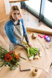 High angle view of young florist arranging flowers and looking. At camera stock photos