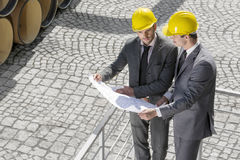 High angle view of young male architects examining blueprint by railings Royalty Free Stock Images