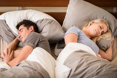 Young man and woman sleeping back-to-back Royalty Free Stock Photos