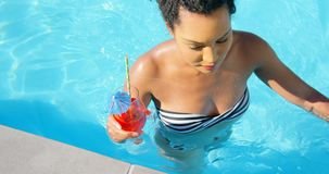 High angle view of young mixed-race woman walking with cocktail glass in swimming pool 4k. High angle view of young mixed-race woman walking with cocktail glass stock footage