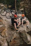 High angle view of young trial bikers relaxing on rocky cliff after ride and shaking. Hands stock images