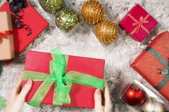 Young woman with Christmas gift. High angle view of a young woman hands holding a Christmas gift with Christmas decoration on the carpet Royalty Free Stock Photos