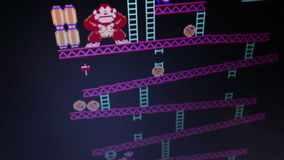 HIgh angle wide shot 'Donkey Kong' retro arcade vintage videogame during game. Play, as seen from player POV; camera dolly to follow some action. Released in stock video