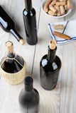 High Angle Wine Still Life. Wine still life shot from a high angle. Five bottles of wine with a cork screw napkin and bowl of corks on a rustic farmhouse style Royalty Free Stock Image