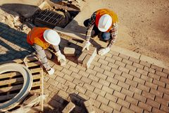 High angle of workers in white helmets arranging paving stones stock photography