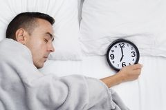 Man in bed grabbing a clock at seven. High angle of a young caucasian man in bed, covered with a soft gray blanket, grabbing a clock at seven royalty free stock photography