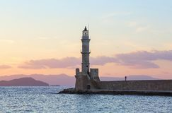 High, beautiful, ancient lighthouse made of bricks. Marvelous sunset lights the sky. Touristic resort Chania, Creete island. High, beautiful, ancient lighthouse royalty free stock image
