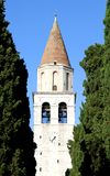 High Bell Tower of the ancient city of AQUILEIA among tall cypre Royalty Free Stock Photo