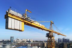 High building construction site. Big industrial tower crane with blue sky amd cityscape on background. Concrete plates weight bala