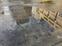 High building reflexion in the wet floor. In the morning after raining Stock Images