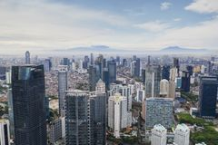 High buildings in misty mountain background. JAKARTA - Indonesia. January 03, 2019: Aerial view of Jakarta city with high buildings in misty mountain background royalty free stock photography