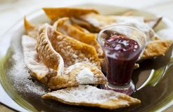 High calories fried dessert with raspberry jam and powdered su Stock Photos