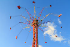 High carousel is whirling on the background of blue sky Stock Photo