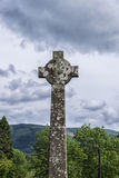 High Celtic Cross with Scottish view. Ancient High Celtic Cross inscribed with biblical verse in Gaelic with backdrop of iconic Scottish scenery Stock Images