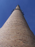 High chimney. A high chimney against a cloudless blue sky, brick building, view from the worm's-eye view royalty free stock photos
