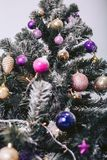 High Christmas tree in decorative toys. High Christmas tree with artificial snow in decorative toys Stock Photo