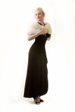 High class woman. Full body of an attractive woman with hair in bun wearing a long formal black gown and a white fur wrap Stock Photography