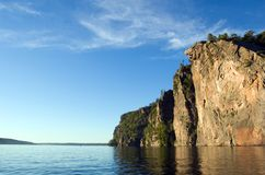 High cliff. At shore of Mazinaw Lake in sunset light Stock Photo