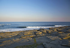 High cliff above the sea, the cliff descends into the sea, many splashing waves and stones. Sunny day Stock Photos