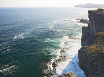 High cliff above the sea, the cliff descends into the sea, many splashing waves and stones. Sunny day Stock Photo