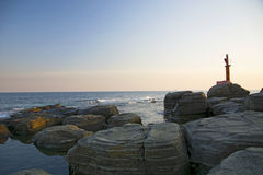 High cliff above the sea, the cliff descends into the sea, many splashing waves and stones. Sunny day Stock Images