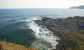 High cliff above the sea, the cliff descends into the sea, many splashing waves and stones. Sunny day Stock Image