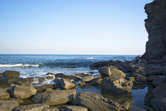 High cliff above the sea, the cliff descends into the sea, many splashing waves and stones. Sunny day Royalty Free Stock Photography