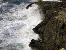 High cliff on the sea with big waves Stock Photos